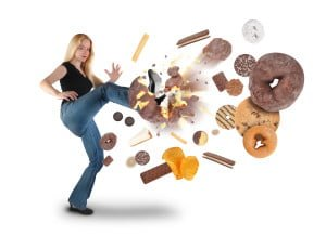 A young woman is kicking a donut on a white background within an assortment of junk food. There are cookies, chips and ice cream. Use it for a diet or nutrition concept.
